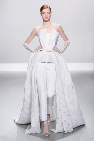White silk gazar peplum gown with embellished open work on train and silk crepe trousers